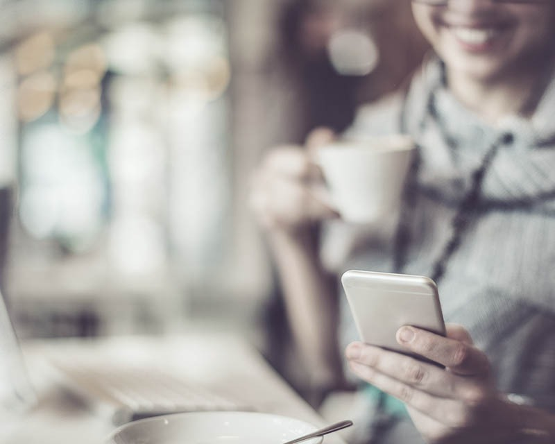 person drinking coffee and holding iphone