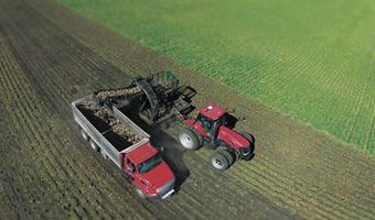 two tractors plowing field